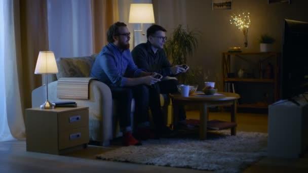 Ve večerních hodinách dva přátelé sedí na pohovce v obývacím pokoji a hraní konkurenční videohry. Jeden z nich vyhraje a on se těší jeho úspěch.