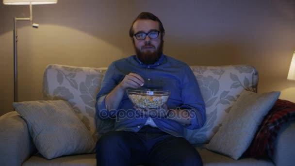 Az ember ül a nappaliban kanapéval