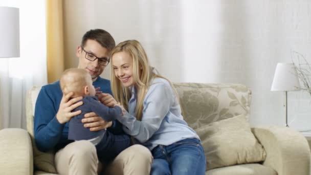 Nella famiglia felice soggiorno seduta su un divano. Bambino si ...