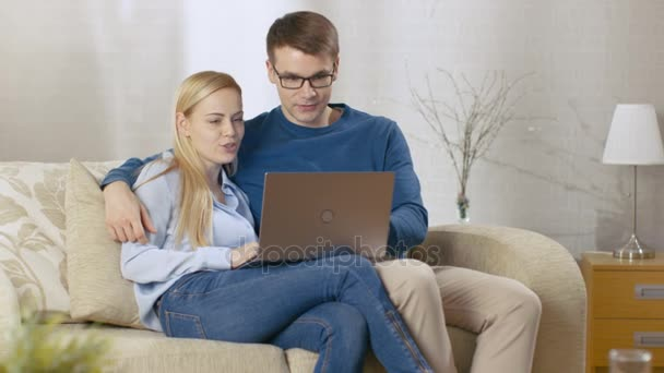 Sweet Couple Sitting on a Sofa in Their Living Room. They're Using Laptop and Smiling. Room is Full of Light.