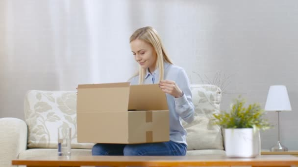 Beautiful Young Woman at Home Opens Cardboard Box while Sitting on a Couch in Her Living Room.