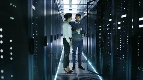 Ženské to technik a mužské Server inženýr, diskutovat o nastavení pracovní datového centra. Muž drží notebook, který stojí před otevřené rozvaděčový Server.