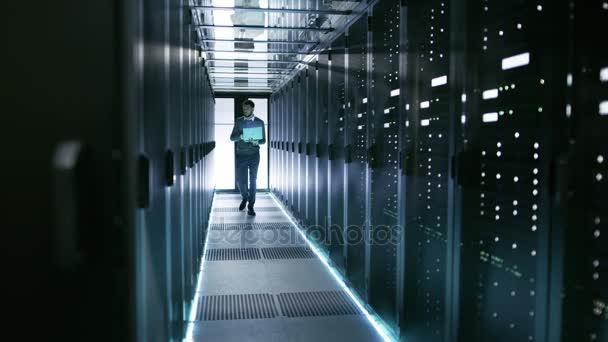 Mužské serveru inženýr procházky s notebookem prostřednictvím pracovní Data centrum plné serverů do racku