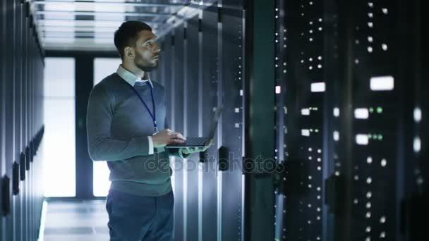 Mužský to technik pracuje na notebooku stojící před otevřené Server Rack skříň ve velkých datacenter.