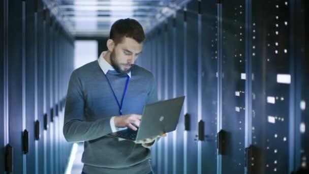 Mužské serveru inženýr pracovat na notebooku v datovém centru, zavření poznámkového bloku a úsměvy.