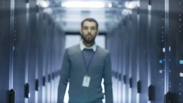 To inženýr chodí do zaostření kamery, úsměvy a založí ruce na hrudi. Pracuje v datovém centru Full Rack serverů.