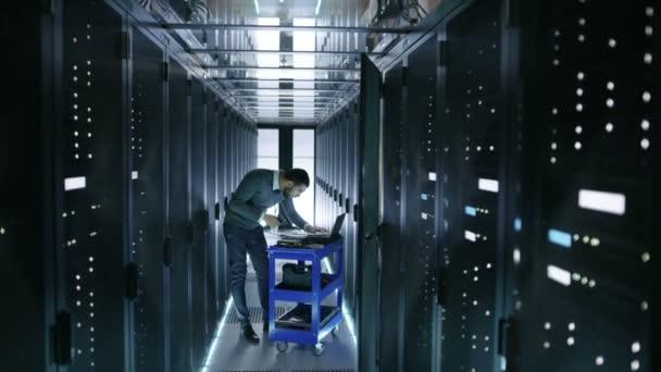 To inženýr pracuje na notebooku a skenuje pevné disky že jsou ležící na vozíku Crash. Pracuje v datovém centru.