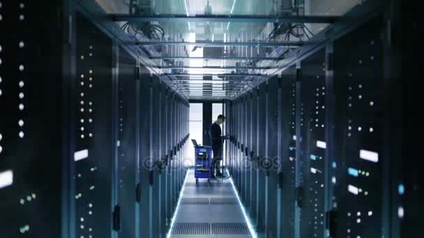 Informatik s Crash vozík klade pevné disky do otevřené skříně serveru kabinetu. Pracuje ve velkých datových Center.