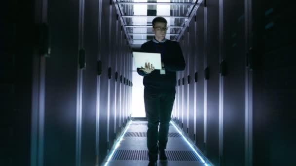 Männliche Kellner Ingenieur geht mit offenen Laptop durch die Reihen der Rack-Server. Er arbeitet in großen, futuristische Rechenzentrum