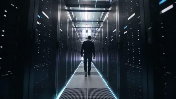 Folgenden Schuss davon Ingenieur zu Fuß durch Rechenzentrum Flur mit Reihen von Rack-Servern. Öffnet Laptop