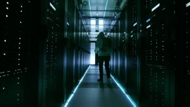 Sledovat záběr maskované Hacker v Hoodie odchází s notebookem v podnikových datových centrech