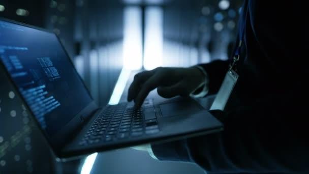 To specialista pracovní pracují na notebooku, je zaměstnanec velkých ultramoderní datového centra.