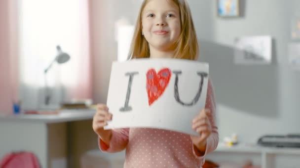 Roztomilá mladá dívka ukazuje zábavné kreslení Miluji tě srdcem ve středu