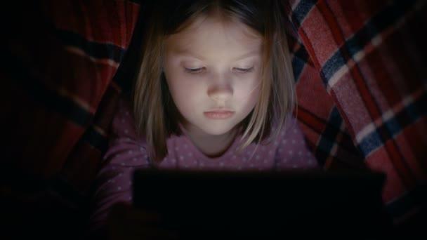 Zvědavá holčička používá tabletový počítač pod krytem, v noci. Displej svítí její obličej