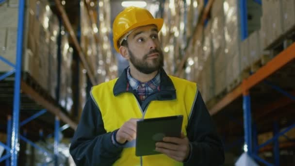Auditor nosit přilbu s tabletovým počítačem počítá zboží ve skladu. Chodí přes řádky skladovací regály se zbožím.