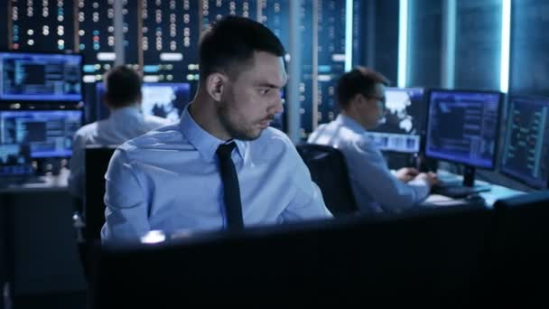 Close-up of Operations Engineer Working on His Computer With Multiple Displays in Monitoring Room. In the Background His Colleagues with Graphics and Various Data on Their Monitors.