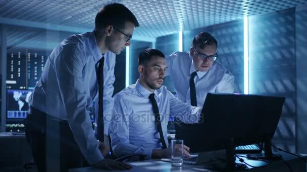 Tři operace inženýři řešení problému v kontrolní místnosti. V systém kontrolní místnost Multitple obrazovky zobrazovat různé údaje.