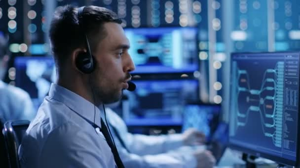 V ovládacím centru systém tým technické podpory poskytuje pokyny s pomocí náhlavní soupravy. Místnost je plná displejů s různými daty na nich.