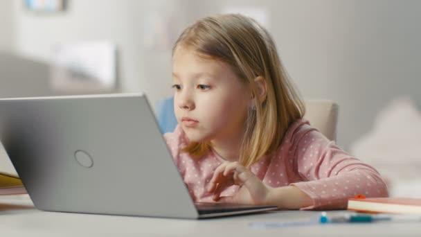 Aranyos fiatal lány használ Laptop számítógép neki fényt szobában az asztalnál ülve.