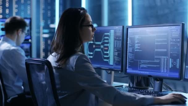 Ženské inženýr řadič dodržuje fungování systému. V pozadí lidí pracovat a monitory zobrazují různé informace.