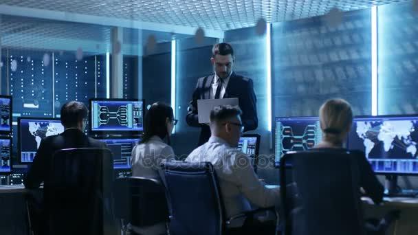 Profesionální technici, pracující v systému ovládací centrum plné monitory a servery. Možná i vládní agentura provádí šetření.