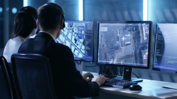 V vládní agentura systém Surveillance Center zaměstnanci trasování zločinec s pomoci of Gps. pokoj je plný displejů s různými daty na nich.