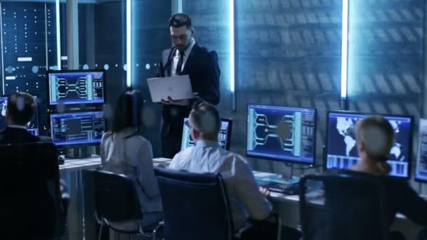 Profesionální technici, pracující v systému ovládací centrum plné monitory a servery. Dohlížitel má Laptop a drží instruktáž. Možná i vládní agentura provádí šetření.