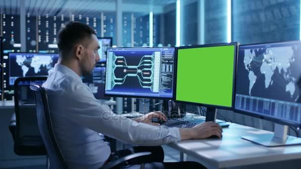 Technické Controller / operátor pracuje na svém pracovišti s více displeji (zelená obrazovka Mock-up). Možné elektrárny / dispečer letiště / přehradní pracovník / vládní dohled / Space Program