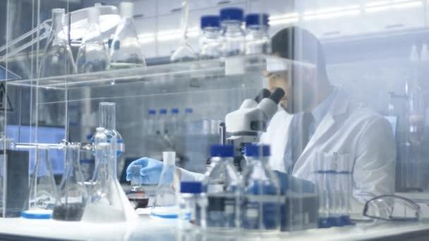 A Modern tudós laboratórium megvizsgálja a főzőpoharat sötét folyadék benne, majd mikroszkóppal bevételt.