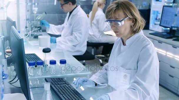 Emelkedett a felvételeket a High Tech Ultra Modern laboratóriumi, a tudósok által végzett kísérletek, működő számítógépeken, látszó-on Mikroszkóp és keverés vegyi anyag.