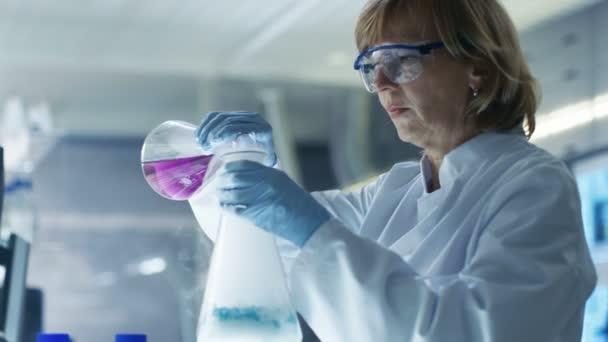 Eine Chemikerin in Schutzbrille mischt in einem Becher rauchende Flüssigkeiten. Sie arbeitet in einem hellen, modernen Labor.