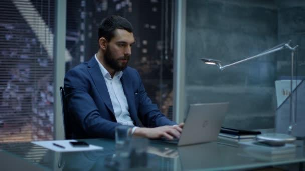 Pozdě v noci podnikatel funguje na notebooku ve své soukromé ordinaci velkoměsta okno zobrazení.