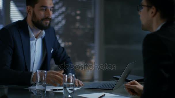 Pozdě v noci podnikatel podnikatel má rozhovor s důležitým klientem, přijdou na dohodu, podepsat smlouvu a potřást rukou. V okně zobrazení pozadí velkoměsta