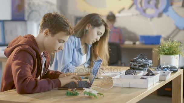 Chlapce programy technické části projektu a dívka píše papír pro jejich věda / robotické / inženýrské třídy ve škole