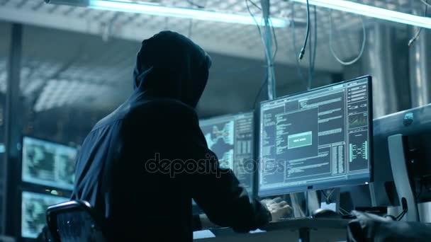 Csuklyás Hacker betör a vállalati adatok szerverek a földalatti rejtekhely. Hely a sötét hangulatot, több monitor kábelek mindenütt.