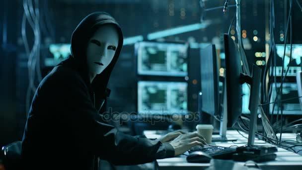 Hacktivisti mascherato organizza attacco violazione massiccia di dati su server aziendali. Sono in luogo segreto sotterraneo circondato da schermi e cavi