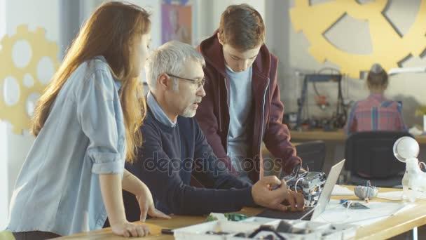 V počítači věda třída učitel zkoumá naprogramovaný Robot ze strany děvče a chlapec
