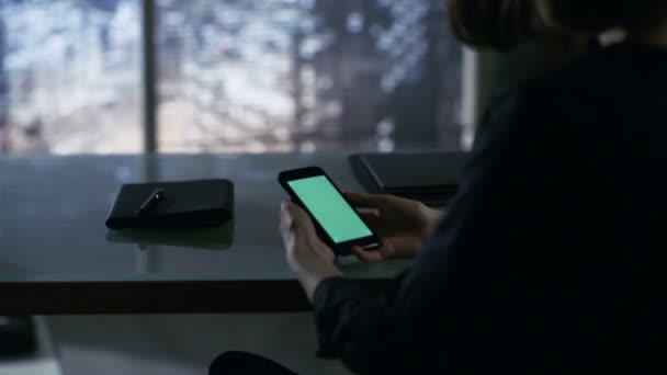 Přes rameno pohled podnikatelka sedí u stolu a Smartphone pomocí zeleným plátnem. Velké město je vidět z okna.