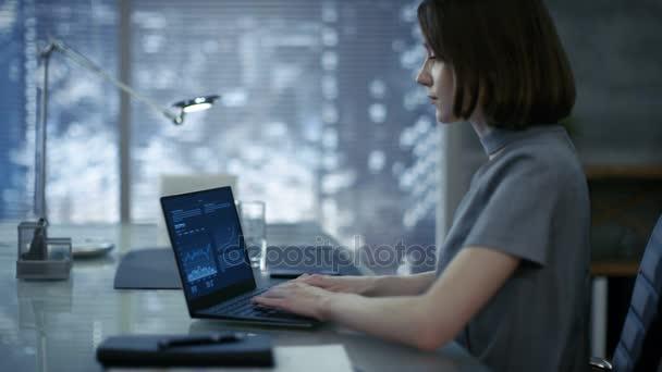 Krásné, stylově oblečená mladá podnikatelka sedí na ni pracovní stůl a typy na přenosném počítači. Její kanceláře vypadá moderní s temné podtóny, velkoměsta za oknem