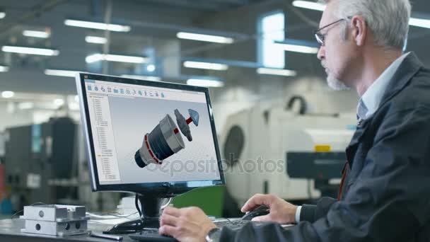 leitender technischer Ingenieur arbeitet an einem CAD-Programm in der Fabrikhalle.