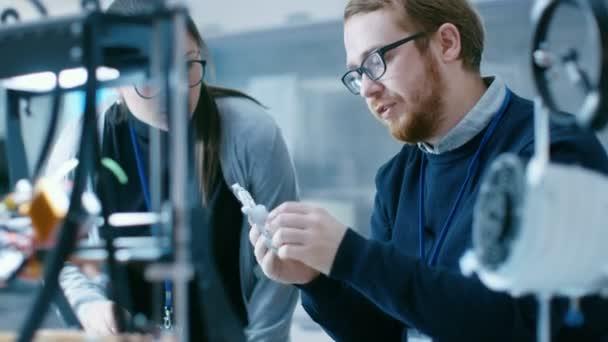 Junge talentierte männliche und weibliche Ingenieure In einem modernen Labor bauen Prototypen mit Hilfe von 3d Drucker.