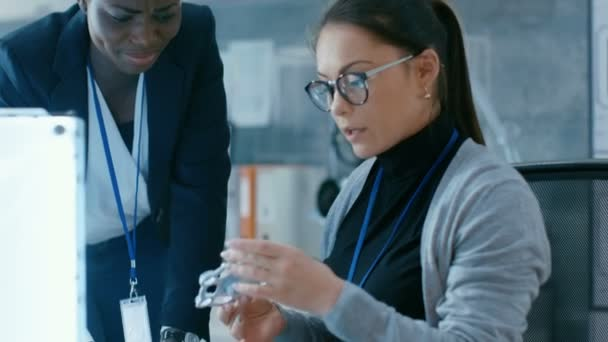 Afrikanisch-amerikanischen und kaukasischen junge Wissenschaftlerinnen diskutieren gedruckten 3D-Modell. Sie sind in einem modernen Labor.