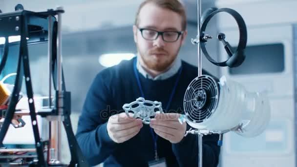Junger talentierte männlichen Ingenieur In einem modernen Labor baut Prototypen mit Hilfe von 3d Drucker.