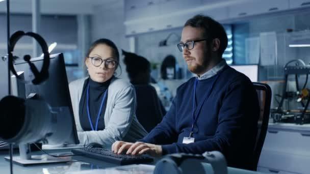 Multi-ethnische Team von jungen weiblichen und männlichen Forschern Eingabe auf ihrem Arbeitsplatzrechner. Sie sind in einem hellen Hightech-Labor.