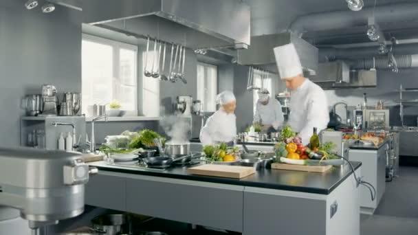 Time-Lapse panoramatický záběr velké restaurace kuchyně a tři kuchaři práci.