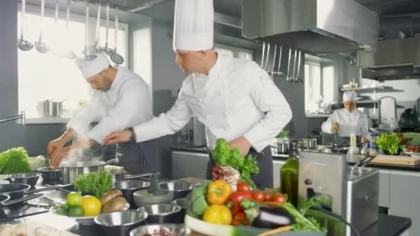 Dva Slavní šéfkuchaři práce jako tým ve velké kuchyni restaurace. Zelenina a ingredience jsou všude, kuchyň vypadá moderní s mnoho z nerezové oceli.