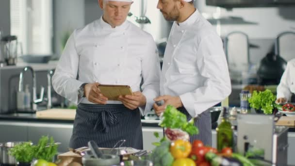 Dva slavné kuchaři výměna myšlenek o Video Blog recept se dívat na tabletu. Oni pracují ve velké kuchyni restaurace.