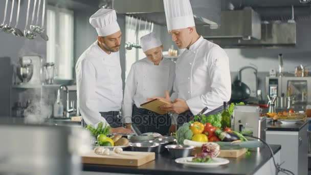 In The Modern Kitchen Team Of Cooks Use Tablet Computer For Recipes They Smile And Have Discussion Kitchen Is Full Of Food Ingredients Vegetables Meat Boiling Soup