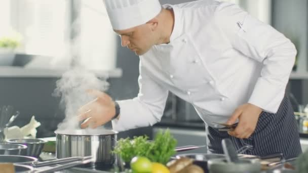 Slavný šéfkuchař restaurace voní páru z hrnce. Jeho příprava jídla v moderní kuchyni