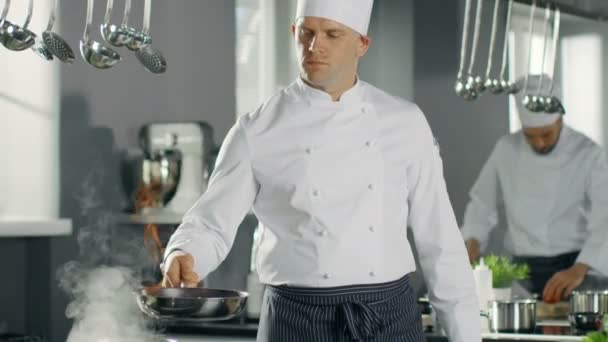 Profesionální kuchař požáry olej na sítě Pan. Flambe, styl vaření. Pracuje v moderní kuchyni s mnoha složek povalovat